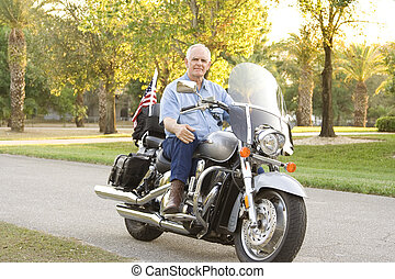 Man On Motorcycle - Senior man sitting on a motorcycle on...