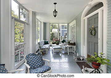 Screened in porch with teal walls in luxury home