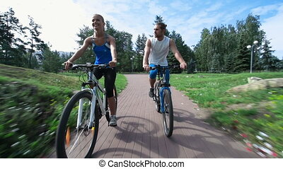 Balance It - Couple of young cyclists riding along the park...