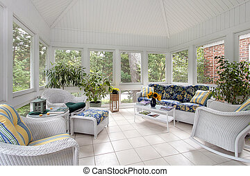 Screened in porch with couch and white tile floor
