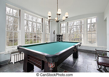 Pool table in sunroom of luxury home