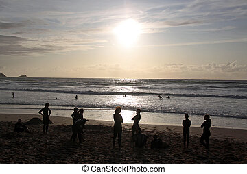 People on the beach at sunset - People swimming in the sea...