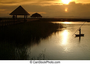 Thai villager punt on lake in Sunset