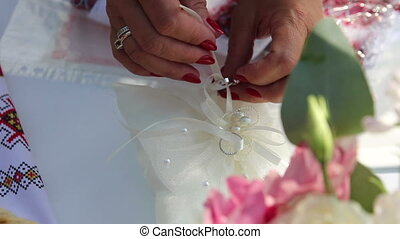 wedding rings on a cushion - women puts wedding rings on a...