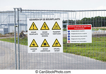 safety signs - shield with safety signs on a fence at a...