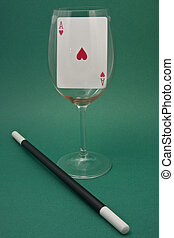 Displays an ace of hearts in a glass with a magic wand