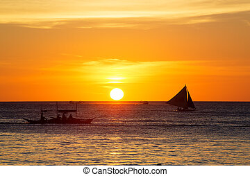 Sailboats at sunset on a tropical sea. Silhouette photo.