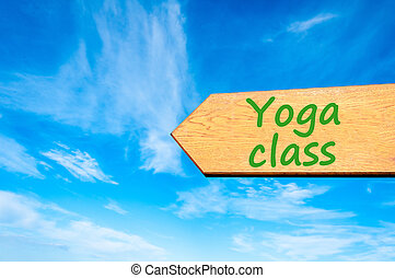 Arrow sign with Yoga Class message - Wood arrow sign against...