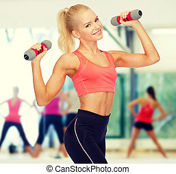 smiling beautiful sporty woman with dumbbells - fitness,...