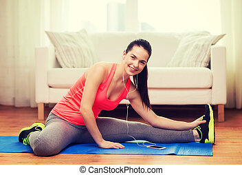 smiling teenage girl streching on floor at home - fitness,...