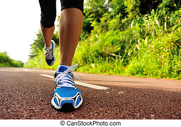 young woman running legs - young fitness woman running at...