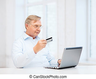old man with laptop and credit card at home - business,...