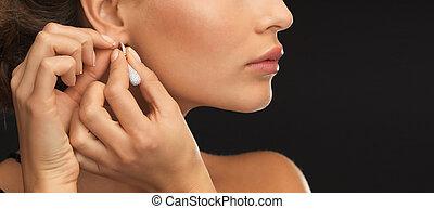 woman wearing shiny diamond earrings - close up of beautiful...