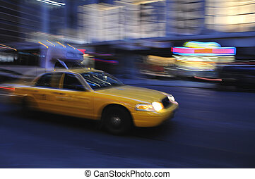 Taxi cab speeding down a city street at night - Taxicab...