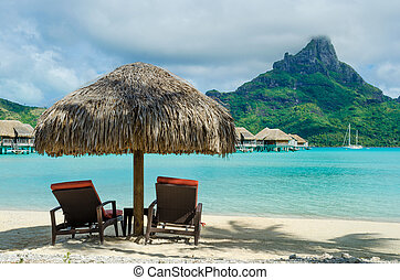 Bora Bora beach - Two sunlounger chairs under a thatched...