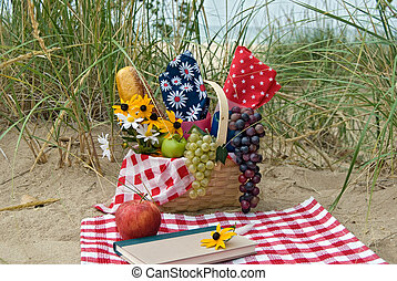 Dune Hideaway - Picnic basket and book in the sand dune.