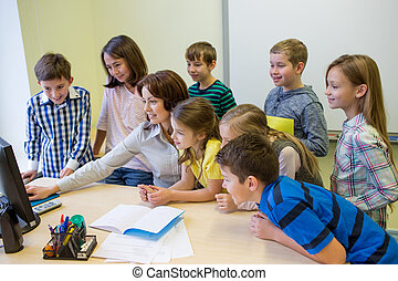group of kids with teacher and computer at school -...
