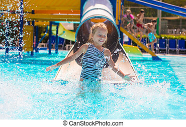 Little girl on water slide at aquapark during summer holiday...