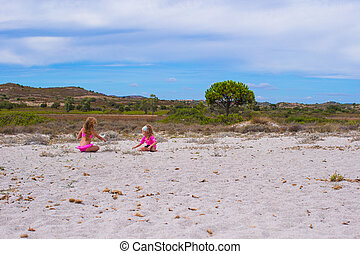 Adorable girls have fun on white beach during vacation -...