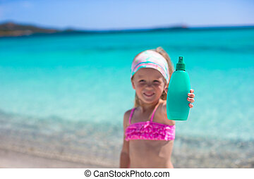 Little adorable girl in swimsuit with suntan lotion bottle -...