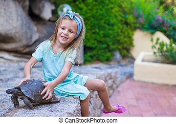 Little adorble happy girl with small turtle outdoors -...