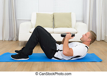 Young Man Exercising With Plate - Happy Young Man Exercising...