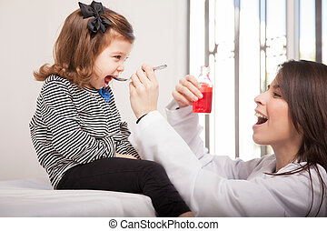 Giving cough syrup to a girl - Pretty pediatrician giving...