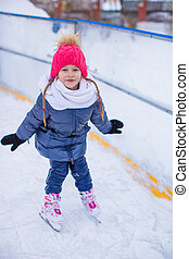 Adorable little girl skating on the ice-rink - Adorable...