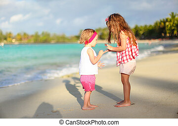 Adorable little girls have fun on white beach during...