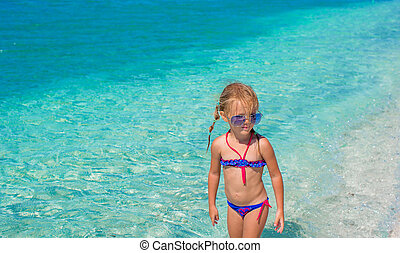Little girl having fun on tropical beach with turquoise ocean water