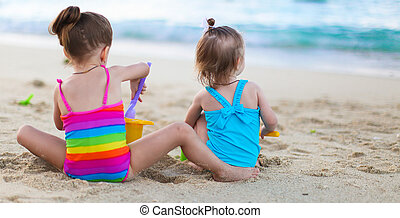 Adorable little girls playing with beach toys during summer...