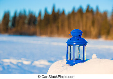 Blue lantern with a candle on white snow outdoor - Beautiful...