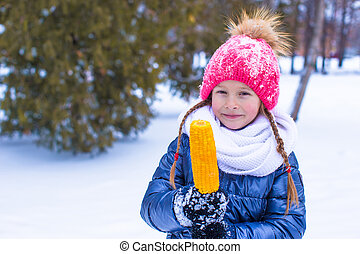 Little adorable girl with sweet corn at winter park