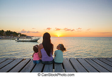 Mom and little daughters silhouette in the sunset on the...
