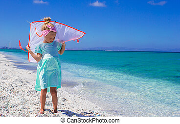 Little happy girl playing with flying kite on tropical beach...