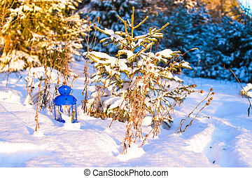 Beautiful blue lantern with a candle on white snow outdoor -...