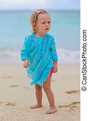Little cute girl on tropical beach with turquoise ocean water