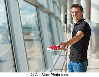 Man holding passports and boarding pass at airport waiting...