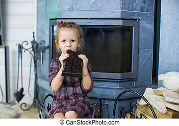 Little cute girl with big chocolate indoor