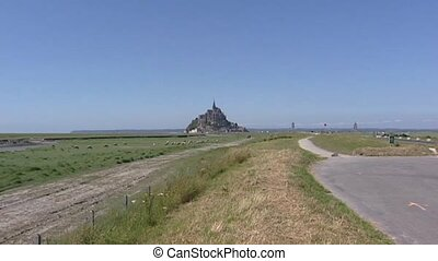Le Mont Saint-Michel in bay behind marshes + zoom in. On the...