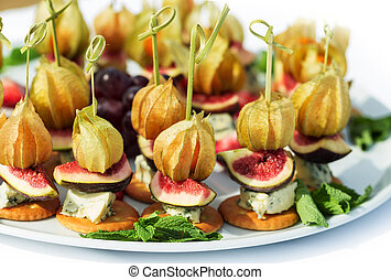 Canapes with physalis, fig, cheese, crackers