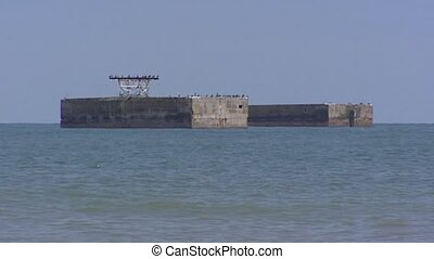 Caisssons Mulberry Harbour in sea, zoom out Gold Beach -...