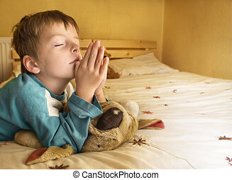 Little boy praying at bedtime.