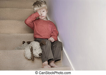 Upset little boy sitting on the stairs