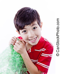 Boy enjoying bubble wrap. - A young boy can't resist the...