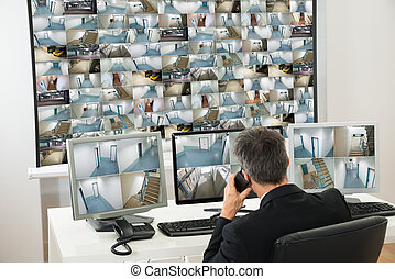 Security System Operator Looking At Cctv Footage While...