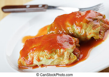 Stuffed cabbage with tomato sauce on white plate