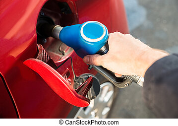Man Refilling The Car With Fuel - Man Refilling The Red Car...