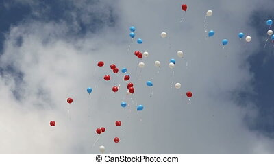Red, white, blue balloons flying in the cloudy sky