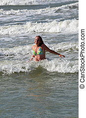 The woman bathes in sea waves.